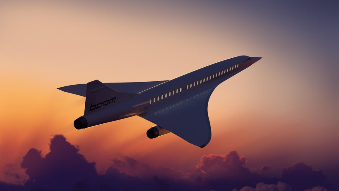 Boom Supersonic aircraft flying into the sunset.